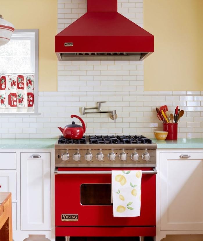 repeindre sa cuisine, murs jaunes, placards et crédence repeintes en blanc, parquet marron, aspirateur et poele couleur rouge, plan de travail vert pâle