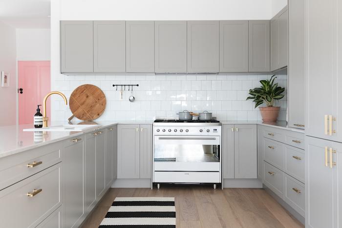 suggestion comment repeindre sa cuisine en gris, poignées dorées, carrelage blanc et porte couleur rose, tapis noir et blans