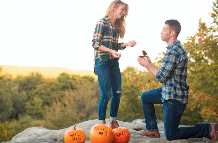 idée surprise mariage en automne, les mots veux tu m epouser gravés sur des citrouilles orange, proposition sur une petite colline dans la forêt