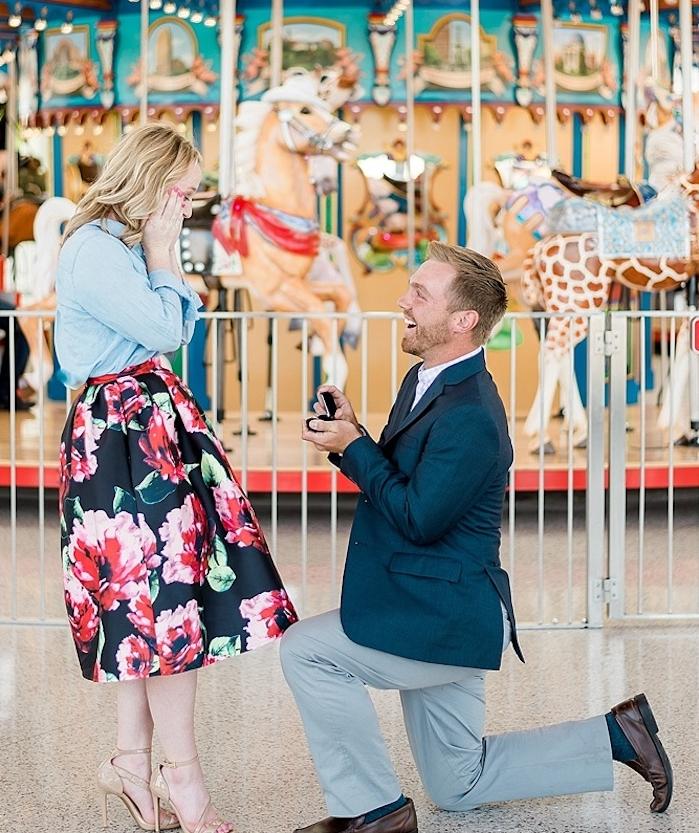 idée de demande en mariage originale dans un parc d attraction, devant un carrousel, femme jupe imprimé fleurie, homme en costume