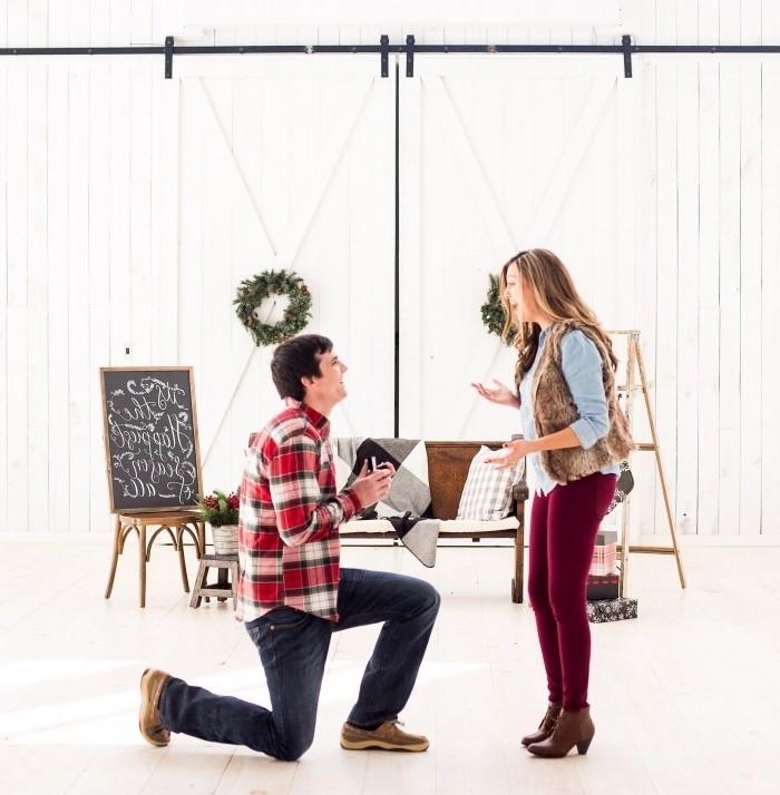 idée surprise mariage dans un hangar blanc, decoration shabby chic, tableau avec message écrit à la craie, canapé en bois, escabeau, couronnes fleuries de noel, proposition à noel