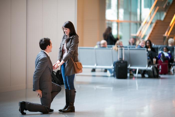 demande de fiancaille à l aéroport dans la salle d attente, femme surprise et homme sur ses jambes