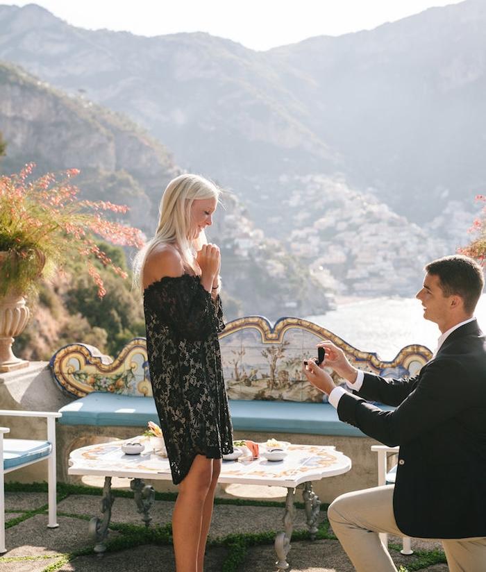 idée de demande en mariage dans un café shabby chic avec vue panoramique sur une montagne, un lac, femme robe noire et home en costume