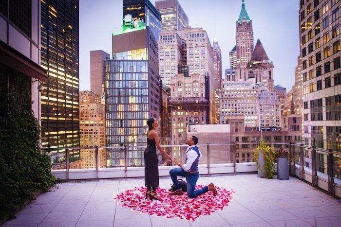 idée surprise mariage au toit d un batiment, milieu urbain, une coeur en pétales de roses et bougies autour