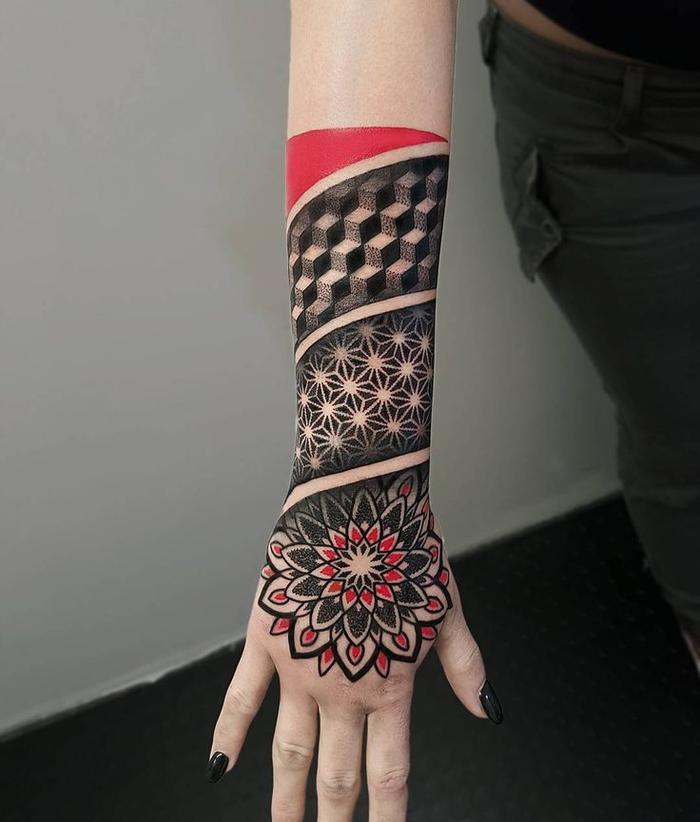 un tatouage femme avant bras graphique à motif fleur de la vie en rouge et noir