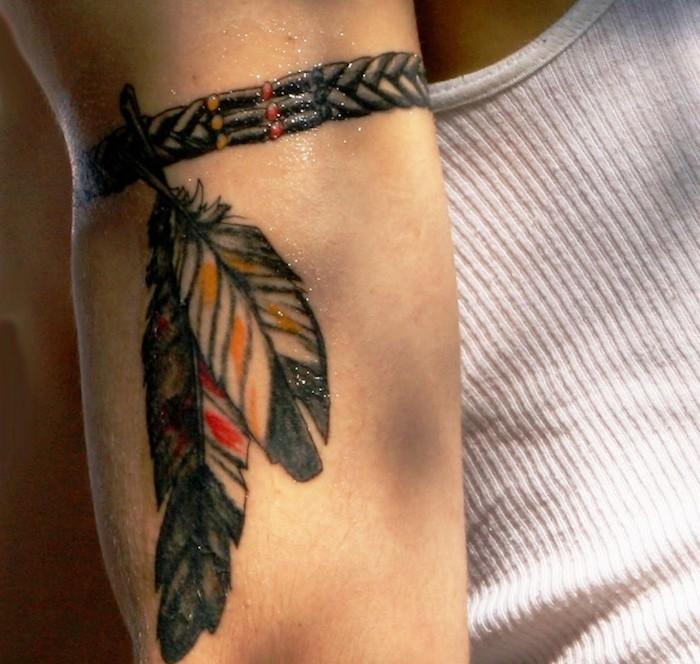 tatouage bras homme, art corporel à motifs bracelet avec plumes, tatouage indien pour le bras