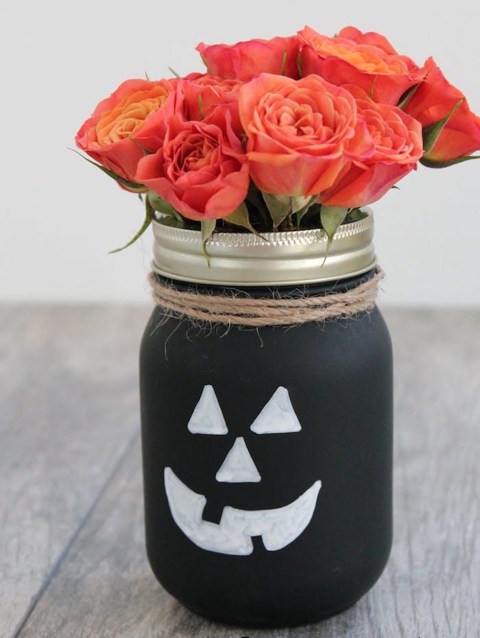 pot de fleur, repeint en noir avec des traits de visage blancs, bricolage halloween avec pot en verre et bouquet de roses dedans