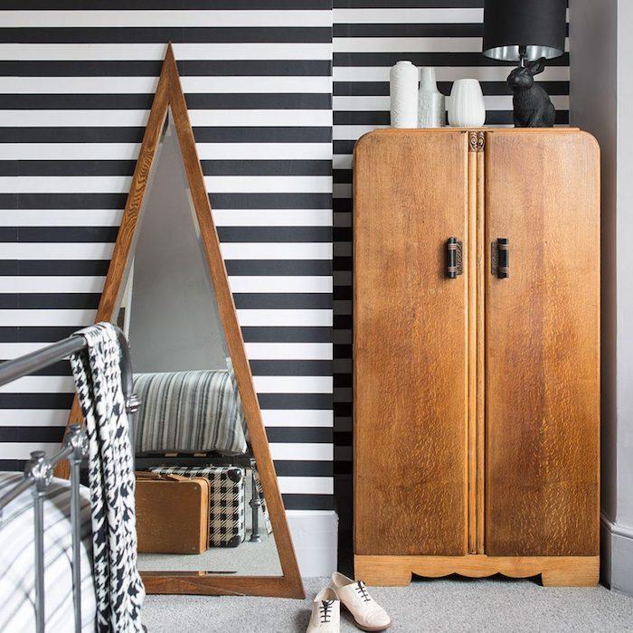 modele de papier peint graphique dans une chambre vintage, armoire bois brut, miroir triangulaire dans un cadre bois, lit metallique