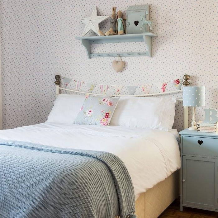 tapisserie chambre blanche à petite fleurs colorées, linge de lit blanc, couverture grise, commode bleue et guirlande fanions, étagère bleu pastel