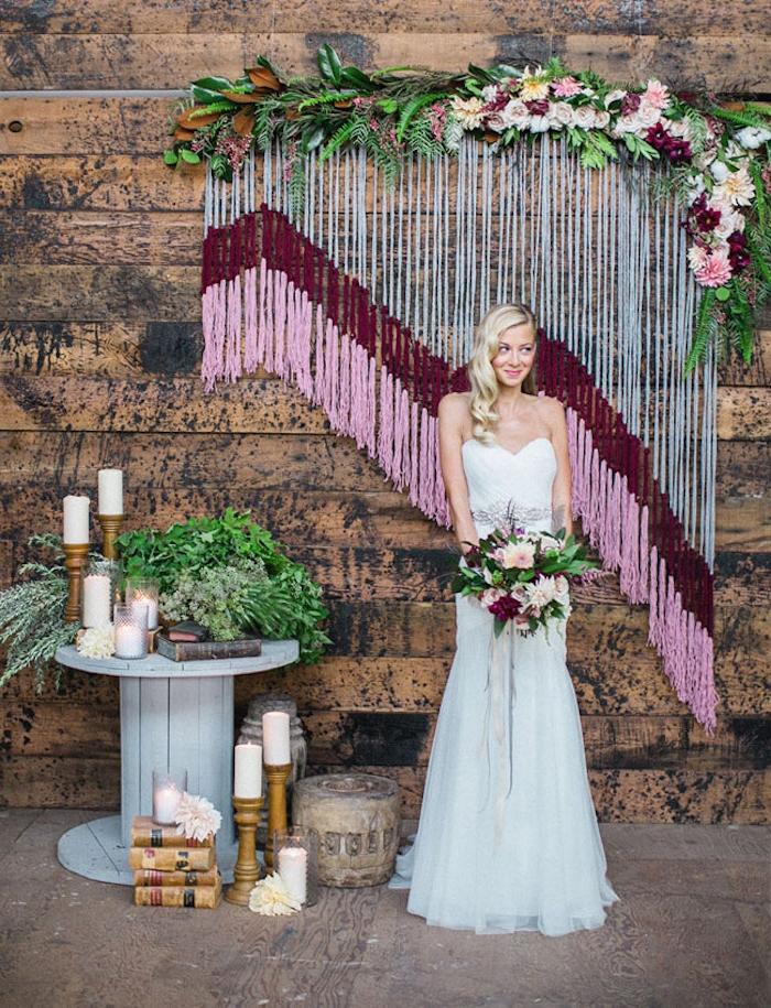 deco salle mariage, macramé et gris, rouge et rose, sur un fond en bois, touret bois deco gris avec bougies, bouquins et fleurs