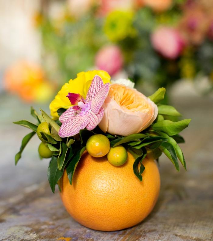 diy mariage tropical, un orange creusé avec un petit bouquet de fleurs dedans, deco simple centre de table mariage
