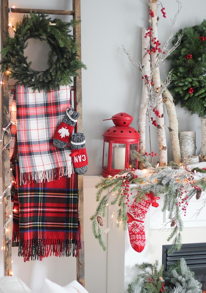 echelle bois deco, porte couvertures en laine, couronne, cheminée blanche, branches de bois, lanternes rouges