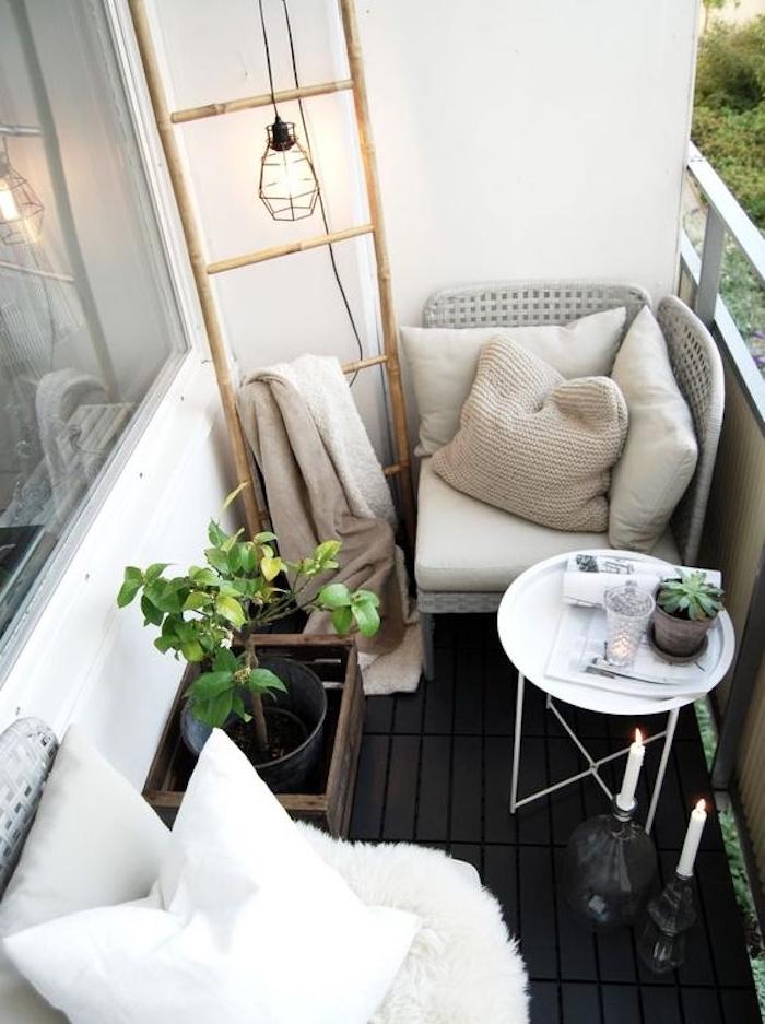 echelle bois deco pour le balcon, fauteuils gris, coussins blancs et gris, rangement textiles, suspension décorative, table basse blanche, bougies, cagettes bois