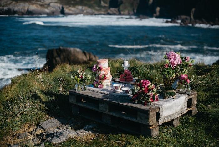 diy mariage deco a faire soi meme, palette sur une falaise, fleurs, gateau, beignets et tasses à thé, style shabby, bougie et nappe en dentelle