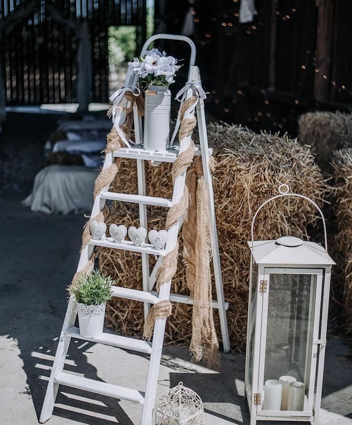 idee mariage decoration en escabeau blanc, décoré de pot de fleur et vase, coeurs blancs, lanterne énorme, bottes de paille, deco mariage champetre
