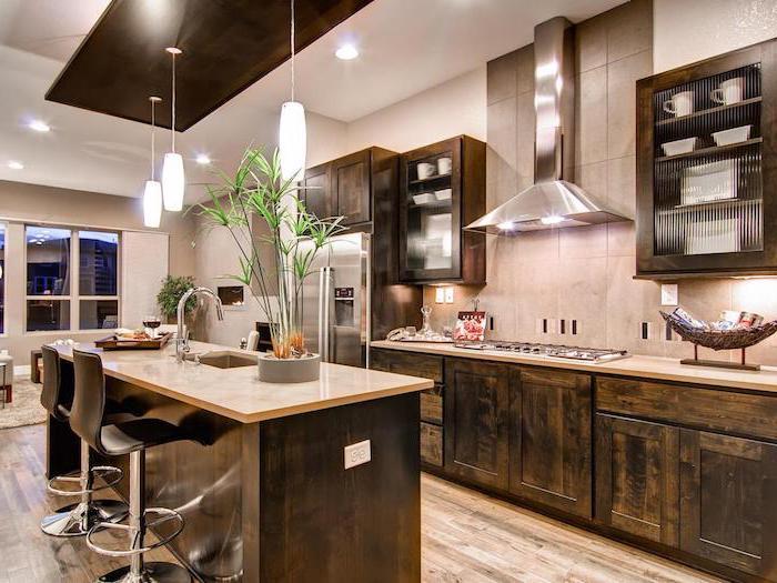 cuisine avec ilot, meubles bas de cuisine en bois foncé avec crédence dalles gris, ilot centrale en bois foncé avec comptoir design marbre