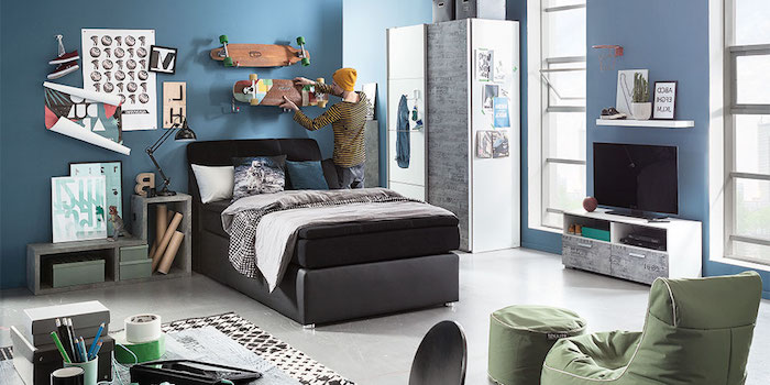 chambre garcon, meubles en bois peints en gris, fauteuil et pouf en tissu vert kaki, tapis blanc et noir à motifs géometriques