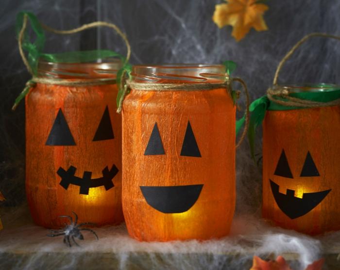 activite halloween avec des pots en verre, customisés de papier crepon collé dessus et des traits de visage noires, bouche et des yeux