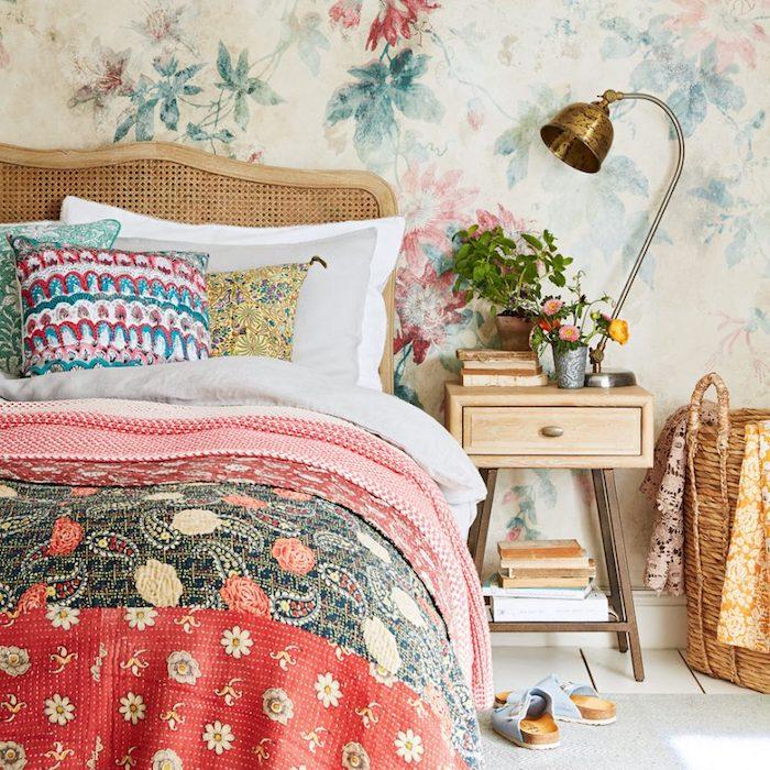papier peint tendance, motifs fleurs en aquarelle, lit bois, linge de lit blanc et gris, couverture et coussins boheme chic colorés, table de nuit bois, rangement livres, plantes, luminaire vintage