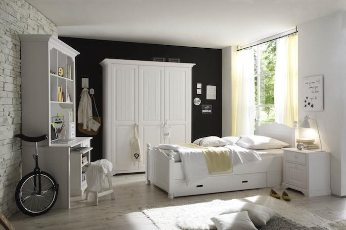chambre à coucher aux murs blancs et noirs, tapis moelleux en blanc avec coussins décoratifs