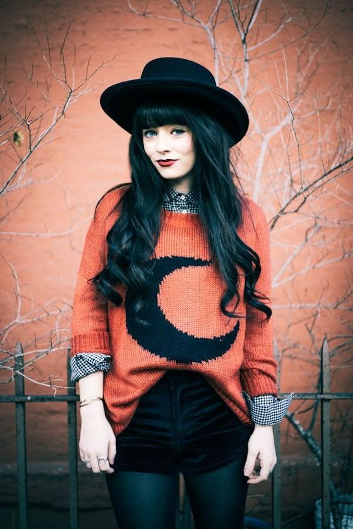 look halloween, deguisment femme, pull orange tricoté avec motif demi lune, shorts et collants noirs, chapeau melon noir
