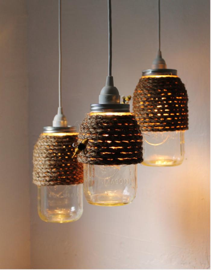 une suspension diy d'aspect vintage et industriel composée de trois bocaux en verre habillés de cordage en chanvre