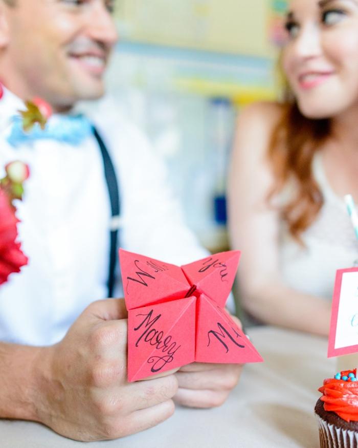message pour mariage, texte veux tu me épouser écrit sur du papier origami, homme et femme en tenue vintage, shooting
