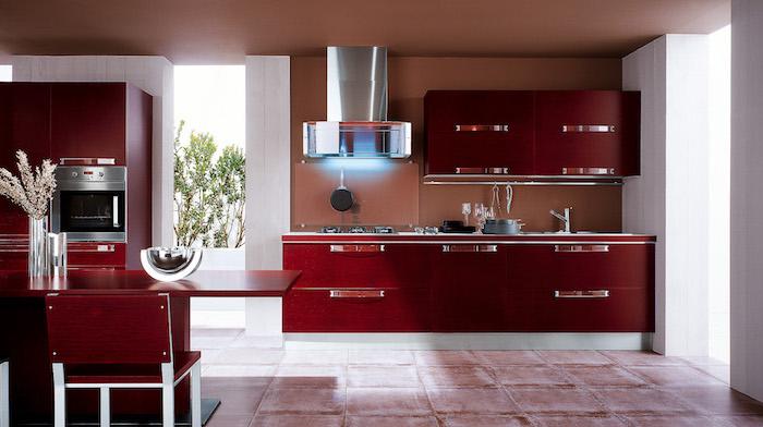 agencement cuisine, carrelage de sol en blanc et rouge, mur de cuisine peints en orange marron, grande fenêtre donnante sur le jardin