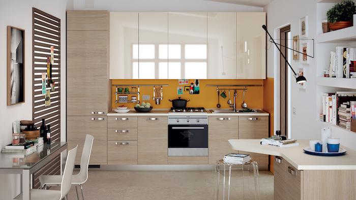 agencement cuisine, meubles de cuisine beige et blanc sans poignées avec crédence orange, petite table d'angle en bois clair