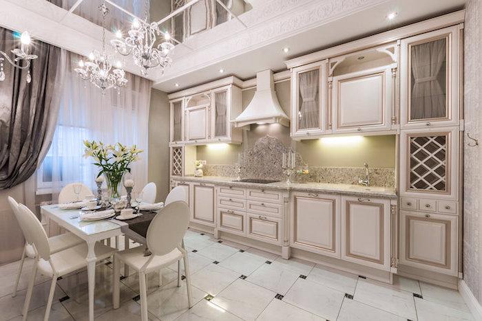 meuble haut cuisine, table à manger blanche avec chaises blanches, plafond blanc avec miroirs et décoration en plâtre