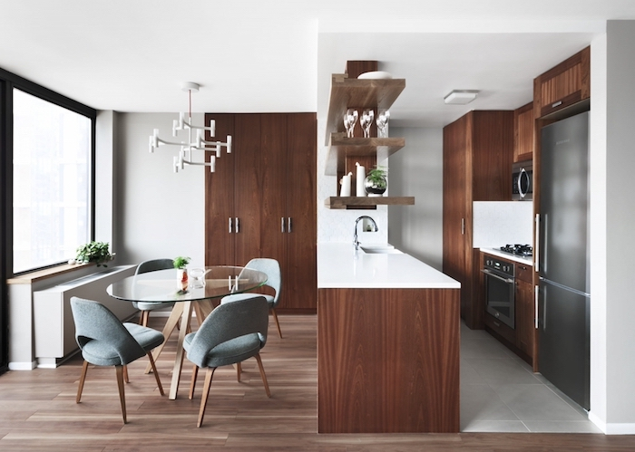 revetement mural cuisine en bois marron, amenagement petite cuisine en longueur, table à manger en verre avec chaises fauteuils