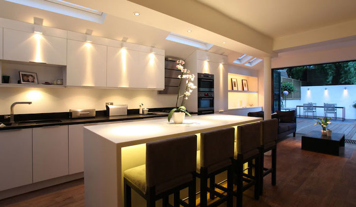 cuisine avec ilot central, meubles de cuisine blanc sans poignées et avec comptoir noir, aménagement de cuisine en longueur