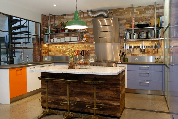 cuisine esprit loft avec des meubles industriels laqués colorés et un îlot central en marbre et bois récup