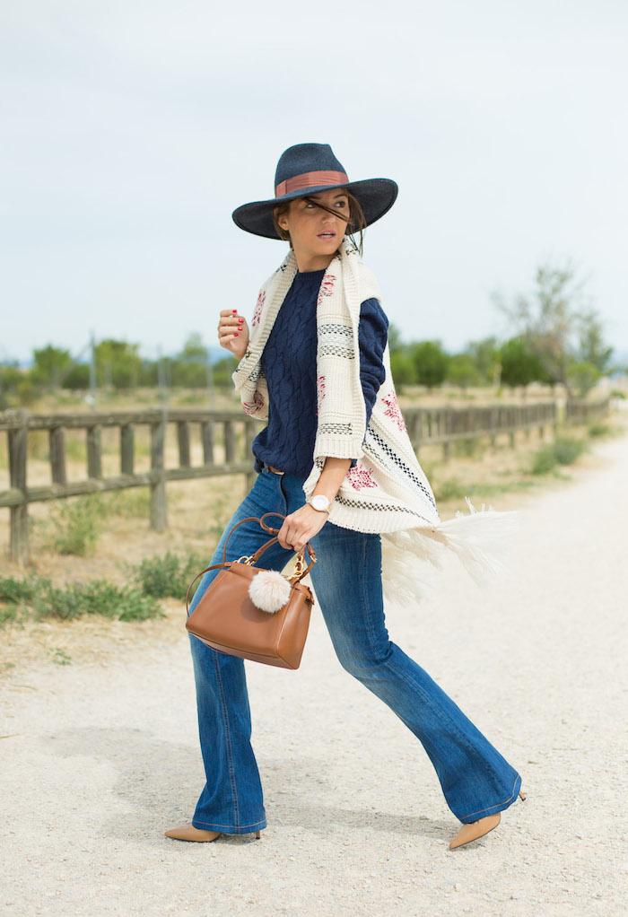 poncho femme blanc à déco rouge et noire avec franges, sac à main en cuir et capeline bleu foncé avec ruban marron