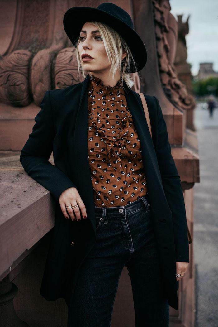 tenue boheme chic, chemise marron avec paire de jeans slim et blazer noir, coiffure cheveux attachés avec mèches devant et capeline noire