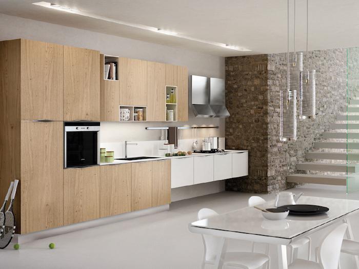 cuisine amenagee, meubles de cuisine en bois et blanc, mur en pierre et escalier en bois blanc, plafond blanc avec éclairage led