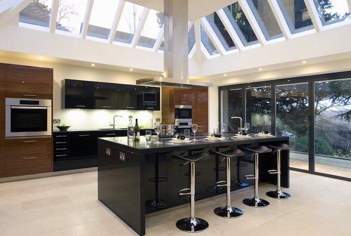 ilot central cuisine en noir avec chaises de bar, plafond blanc avec fenêtres et éclairage led, meubles de cuisine en noir et bois foncé