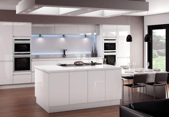 meuble bas cuisine sans poignées en blanc avec éclairage néon en bleu, canapé en cuir noir et lampes suspendues noires