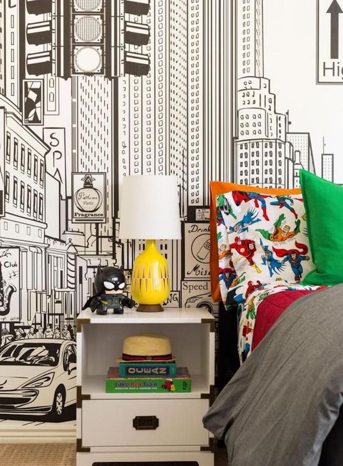 idee deco chambre enfant garçon, papier peint graphique tendance, dessin paysage new york noir et blanc, linge de lit orange, rouge, gris et vert, coussins motif héros bandes dessinés