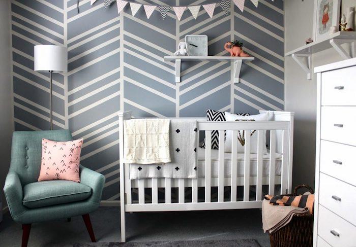 papier peint tendance gris avec des lignes blanches, lit bébé blanc, fauteuil bleu canard, guirlande fanions, commode blanc