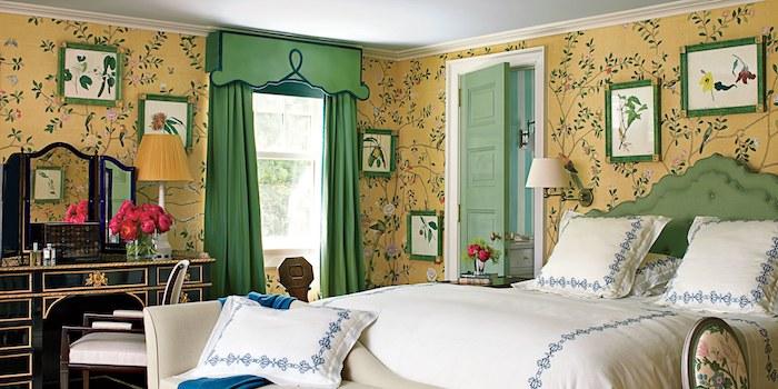 chambre baroque, décorée de papier peint vintage jaune à motifs branches fleuries, coiffeuse noire, linge de lit blanc avec détails bleus
