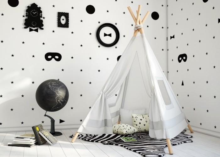papier peint scandinave graphique dans une chambre enfant design nordique, mur blanc, motif étoiles et masques, tipi enfant, tapis zebre, parquet blanchi