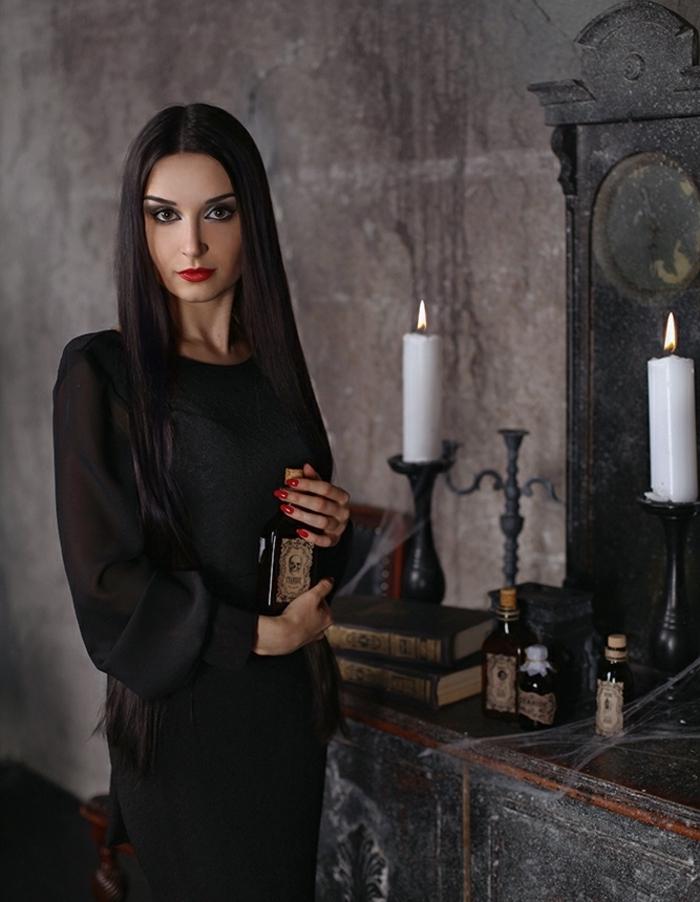Idée tenue morticia addams, robe noire avec manches transparentes, livres grimoires, bougies fioles sur le fond, cheveux lisses longues teinte pale