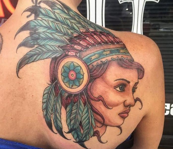 tatouage indien d amérique, art corporel sur dos féminin avec visage femme aux cheveux rouges et plumes bleus