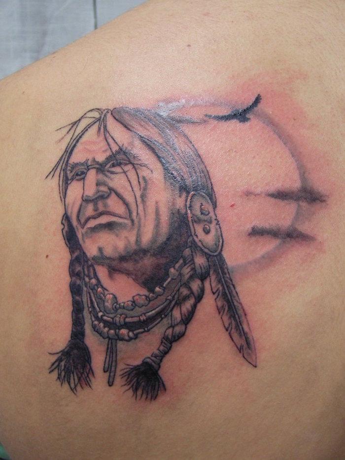 tatouage pour homme sur le dos, dessin en encre avec visage homme autochtone et plumes dans les cheveux