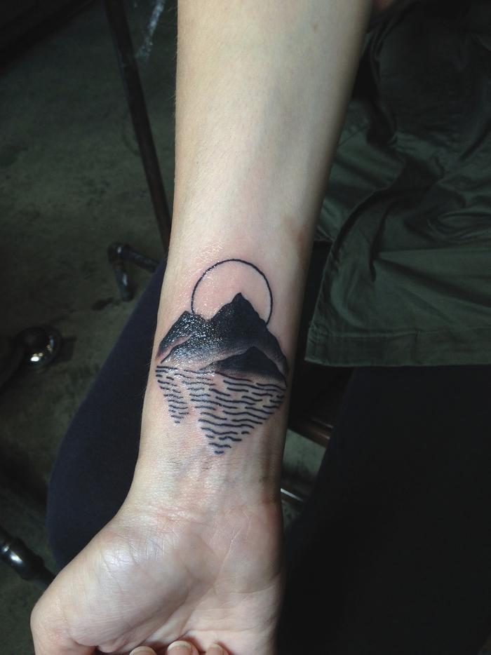 un tatouage paysage graphique et géométrique représentant la mer, l'océan et le soleil