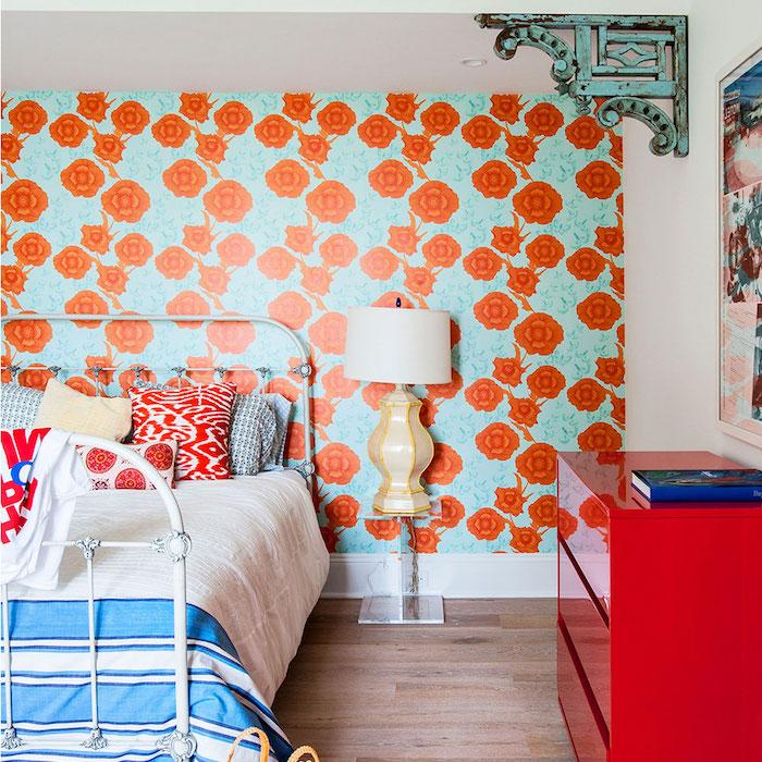 modele de papier peint vintage avec imprimé de fleurs orange sur un fond bleu, linge de lit blanc et bleu et coussins blanc, rouge et bleu, parquet bois clair, commode rouge
