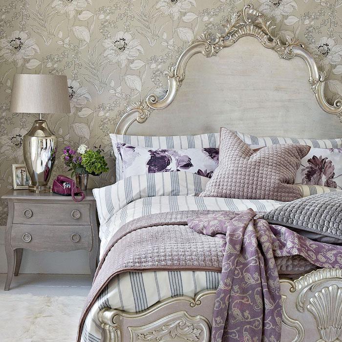 exemple de papier peint baroque, revetement mural gris avec de fleurs blanches, lit baroque arabesques, linge de lit blanc, bleu et violet, tapis moelleux, table de nuit grise