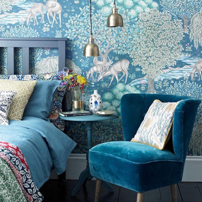 modele de tapisserie chambre bleue avec motif foret avec arbres et animaux, lit gris, linge de lit bleu et à imprimé floral, fauteuil bleu canard