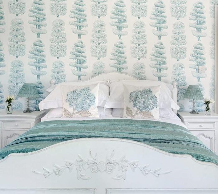 modele de tapisserie chambre, arbres vertes sut un fond blanc, lit blanc avec couverture bleu canard, exemple de papier peint baroque
